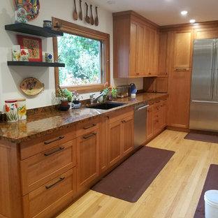ロサンゼルスの中サイズのエクレクティックスタイルのおしゃれなキッチン (アンダーカウンターシンク、シェーカースタイル扉のキャビネット、中間色木目調キャビネット、クオーツストーンカウンター、シルバーの調理設備の、淡色無垢フローリング、黄色い床) の写真