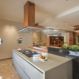 Imagen de cocina asiática, abierta, con armarios con paneles lisos, puertas de armario grises, electrodomésticos negros, suelo marrón y encimeras grises