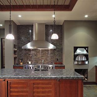 ロサンゼルスの大きいアジアンスタイルのおしゃれなキッチン (アンダーカウンターシンク、フラットパネル扉のキャビネット、中間色木目調キャビネット、御影石カウンター、グレーのキッチンパネル、ボーダータイルのキッチンパネル、シルバーの調理設備の、スレートの床) の写真