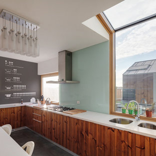 Trendy l-shaped enclosed kitchen photo in Other with an undermount sink, medium tone wood cabinets and glass sheet backsplash