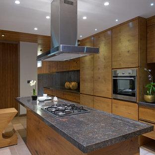 На фото: большая кухня в восточном стиле с плоскими фасадами, коричневыми фасадами, техникой из нержавеющей стали, бежевым полом и коричневой столешницей с