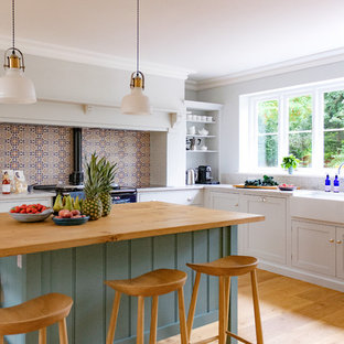 Design ideas for a large traditional u-shaped kitchen/diner in Hertfordshire with shaker cabinets, white cabinets, engineered stone countertops, stainless steel appliances, medium hardwood flooring, an island, brown floors, grey worktops, a belfast sink, multi-coloured splashback and cement tile splashback.