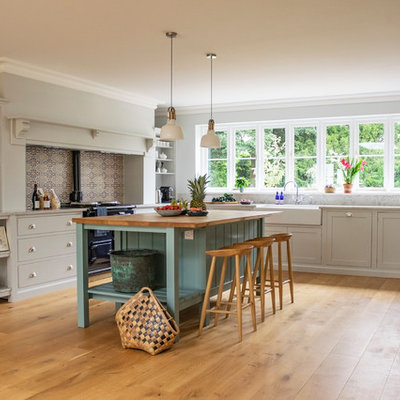 Inspiration for a large transitional u-shaped medium tone wood floor and brown floor eat-in kitchen remodel in Hertfordshire with a double-bowl sink, shaker cabinets, white cabinets, quartz countertops, gray backsplash, stone slab backsplash, stainless steel appliances, an island and gray countertops
