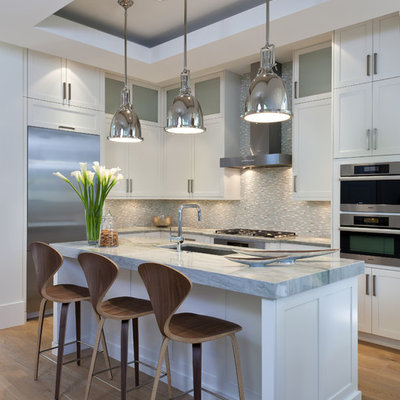 Kitchen - mid-sized transitional l-shaped medium tone wood floor kitchen idea in Miami with an undermount sink, shaker cabinets, white cabinets, gray backsplash, mosaic tile backsplash, stainless steel appliances and an island