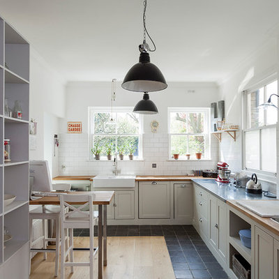 Example of a mid-sized classic l-shaped black floor eat-in kitchen design in London with shaker cabinets, gray cabinets, wood countertops, white backsplash, subway tile backsplash, brown countertops and a farmhouse sink