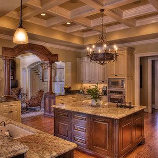 Inspiration pour une grand cuisine traditionnelle en U fermée avec un électroménager en acier inoxydable, un plan de travail en granite, un évier encastré, un placard avec porte à panneau surélevé, des portes de placard beiges, une crédence beige, une crédence en travertin, un sol en bois brun et un îlot central.