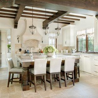 Idéer för ett stort medelhavsstil kök, med beige stänkskydd, kalkstensgolv, en köksö, luckor med infälld panel, vita skåp, integrerade vitvaror, en rustik diskho, bänkskiva i kvartsit och stänkskydd i kalk