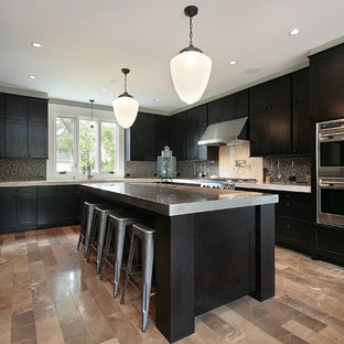 This is an example of a large modern u-shaped eat-in kitchen in Jacksonville with an undermount sink, stainless steel appliances, with island, black cabinets, stainless steel benchtops, blue splashback, glass sheet splashback, marble floors, multi-coloured floor, shaker cabinets and multi-coloured benchtop.