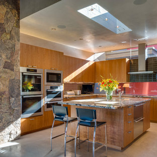 Large contemporary u-shaped kitchen in Albuquerque with flat-panel cabinets, medium wood cabinets, grey splashback, subway tile splashback, stainless steel appliances, with island, concrete floors, an undermount sink and soapstone benchtops.