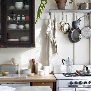 ニューヨークの小さいカントリー風おしゃれなアイランドキッチン (ガラス扉のキャビネット、大理石カウンター、白い調理設備、白いキッチンカウンター、濃色木目調キャビネット、白いキッチンパネル) の写真