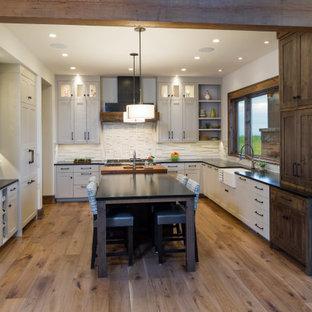 他の地域の中くらいのラスティックスタイルのおしゃれなキッチン (アンダーカウンターシンク、シェーカースタイル扉のキャビネット、グレーのキャビネット、ソープストーンカウンター、白いキッチンパネル、大理石のキッチンパネル、シルバーの調理設備、無垢フローリング、茶色い床、黒いキッチンカウンター) の写真