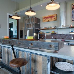 Idée de décoration pour une grand cuisine ouverte parallèle urbaine avec un évier 2 bacs, des portes de placard en bois vieilli, un plan de travail en verre recyclé, une crédence métallisée, un électroménager en acier inoxydable, béton au sol et un îlot central.