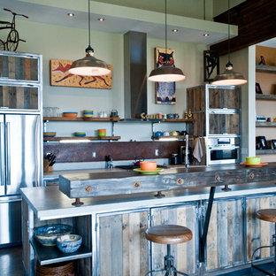 Exempel på ett stort industriellt kök, med skåp i slitet trä, rostfria vitvaror, en köksö, en dubbel diskho, bänkskiva i återvunnet glas, stänkskydd med metallisk yta, betonggolv och öppna hyllor