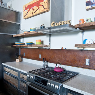 Photo of a large industrial galley open plan kitchen in Other with a double-bowl sink, distressed cabinets, recycled glass benchtops, metallic splashback, stainless steel appliances, concrete floors and with island.