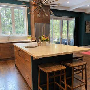 Inspiration for a large l-shaped open plan kitchen in Toronto with an undermount sink, flat-panel cabinets, medium wood cabinets, quartz benchtops, white splashback, stainless steel appliances, medium hardwood floors, with island, brown floor and white benchtop.