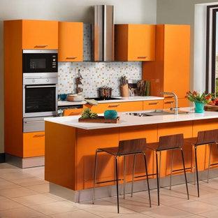 サンフランシスコの広いおしゃれなキッチン (ドロップインシンク、フラットパネル扉のキャビネット、オレンジのキャビネット、御影石カウンター、マルチカラーのキッチンパネル、セラミックタイルのキッチンパネル、シルバーの調理設備、セラミックタイルの床) の写真