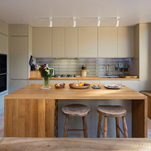 Inspiration for a transitional l-shaped eat-in kitchen in London with a double-bowl sink, flat-panel cabinets, beige cabinets, wood benchtops, grey splashback, glass tile splashback, black appliances, brick floors, with island, red floor and brown benchtop.
