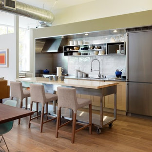 Photo of an industrial single-wall open plan kitchen in Los Angeles with stainless steel benchtops, open cabinets, an integrated sink, stainless steel cabinets, white splashback, stone slab splashback and stainless steel appliances.