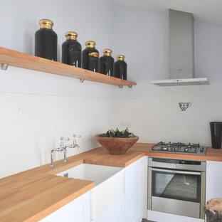 ロンドンの小さいモダンスタイルのおしゃれなキッチン (エプロンフロントシンク、フラットパネル扉のキャビネット、グレーのキャビネット、木材カウンター、白いキッチンパネル、磁器タイルのキッチンパネル、シルバーの調理設備の、クッションフロア、アイランドなし) の写真