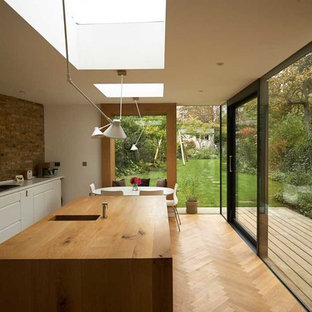 Medium sized contemporary single-wall enclosed kitchen in London with a double-bowl sink, flat-panel cabinets, white cabinets, wood worktops, light hardwood flooring, an island and beige floors.