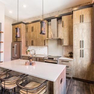 ニューオリンズのコンテンポラリースタイルのおしゃれなキッチン (ドロップインシンク、フラットパネル扉のキャビネット、ベージュのキャビネット、白いキッチンパネル、レンガのキッチンパネル、シルバーの調理設備の、濃色無垢フローリング、茶色い床、白いキッチンカウンター) の写真