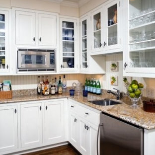 This is an example of a mid-sized traditional galley eat-in kitchen in DC Metro with a drop-in sink, glass-front cabinets, white cabinets, soapstone benchtops, white splashback, stone slab splashback, stainless steel appliances, dark hardwood floors and no island.