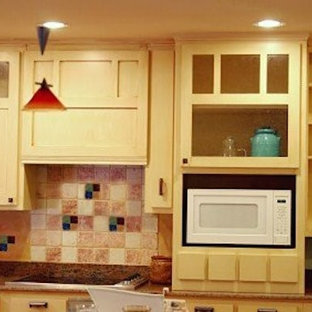 Küche mit Glasfronten, gelben Schränken, Granit-Arbeitsplatte, Küchenrückwand in Rot, Rückwand aus Zementfliesen und weißen Elektrogeräten in Boston