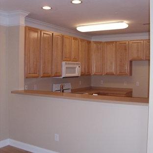 チャールストンのおしゃれなキッチン (ルーバー扉のキャビネット、中間色木目調キャビネット、木材カウンター、ベージュキッチンパネル) の写真