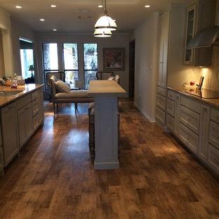 ダラスのエクレクティックスタイルのおしゃれなキッチン (シェーカースタイル扉のキャビネット、グレーのキャビネット、御影石カウンター、ベージュキッチンパネル、ボーダータイルのキッチンパネル、シルバーの調理設備の、無垢フローリング) の写真