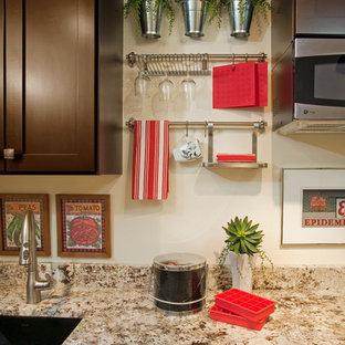 Modern inredning av ett litet kök, med en enkel diskho, skåp i shakerstil, skåp i mörkt trä, granitbänkskiva, beige stänkskydd, rostfria vitvaror, heltäckningsmatta och beiget golv