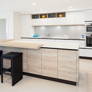 Contemporary kitchen in Perth with flat-panel cabinets, white cabinets, grey splashback, with island, an undermount sink, glass sheet splashback and stainless steel appliances.