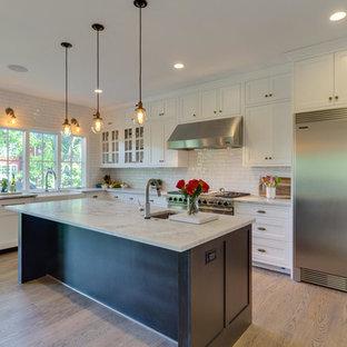 Esempio di una cucina stile americano di medie dimensioni con lavello sottopiano, ante bianche, top in marmo, paraspruzzi bianco, paraspruzzi con piastrelle in ceramica, elettrodomestici in acciaio inossidabile, pavimento in legno massello medio, isola e ante in stile shaker