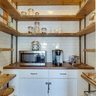 ワシントンD.C.の中サイズのカントリー風おしゃれなキッチン (白いキャビネット、木材カウンター、白いキッチンパネル、シルバーの調理設備の、無垢フローリング、サブウェイタイルのキッチンパネル、アンダーカウンターシンク、シェーカースタイル扉のキャビネット) の写真