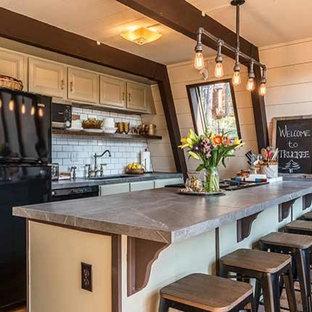 サクラメントの小さいエクレクティックスタイルのおしゃれなキッチン (シングルシンク、緑のキャビネット、タイルカウンター、白いキッチンパネル、サブウェイタイルのキッチンパネル、黒い調理設備、ラミネートの床、茶色い床、グレーのキッチンカウンター) の写真