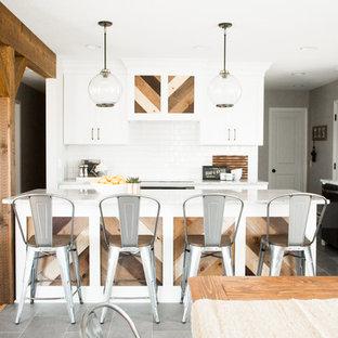 ミネアポリスの中サイズのインダストリアルスタイルのおしゃれなキッチン (エプロンフロントシンク、シェーカースタイル扉のキャビネット、白いキャビネット、御影石カウンター、白いキッチンパネル、セラミックタイルのキッチンパネル、シルバーの調理設備の、セラミックタイルの床、グレーの床) の写真