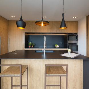 Modelo de cocina nórdica, de tamaño medio, con armarios con paneles lisos, salpicadero negro, electrodomésticos de acero inoxidable, una isla, puertas de armario de madera clara, fregadero de un seno y encimeras negras
