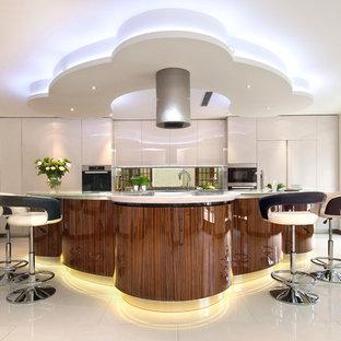 Geräumige Moderne Wohnküche in U-Form mit flächenbündigen Schrankfronten, hellbraunen Holzschränken, Mineralwerkstoff-Arbeitsplatte, Küchenrückwand in Metallic, Glasrückwand, Küchengeräten aus Edelstahl, Porzellan-Bodenfliesen und Kücheninsel in London