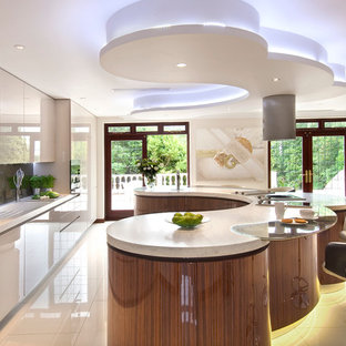 Design ideas for an expansive modern u-shaped eat-in kitchen in London with an integrated sink, flat-panel cabinets, medium wood cabinets, solid surface benchtops, metallic splashback, glass sheet splashback, stainless steel appliances, porcelain floors and with island.