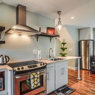 Inspiration for a small arts and crafts single-wall open plan kitchen in Nashville with a double-bowl sink, flat-panel cabinets, white cabinets, wood benchtops, stainless steel appliances and medium hardwood floors.