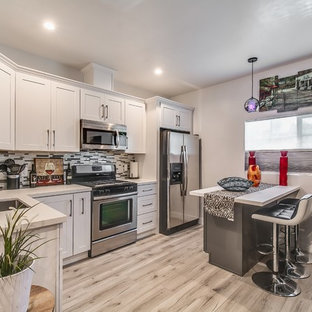 Small open concept kitchen designs - Small l-shaped medium tone wood floor and brown floor open concept kitchen photo in Los Angeles with shaker cabinets, white cabinets, multicolored backsplash, glass sheet backsplash, stainless steel appliances, an island and white countertops