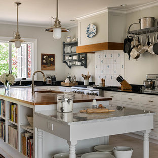 Design ideas for a mid-sized country u-shaped open plan kitchen in Bridgeport with shaker cabinets, white cabinets, granite benchtops, white splashback, stainless steel appliances, light hardwood floors, with island, beige floor, porcelain splashback and a farmhouse sink.