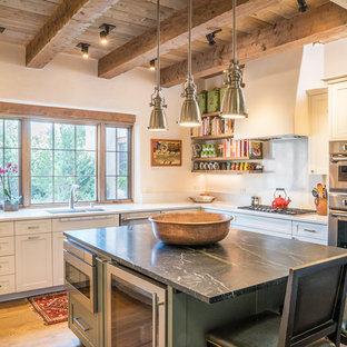 Diseño de cocina en L, de estilo americano, con fregadero bajoencimera, armarios estilo shaker, puertas de armario blancas, electrodomésticos de acero inoxidable, suelo de madera en tonos medios, una isla y suelo marrón