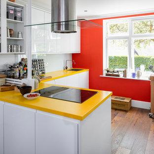 Immagine di una cucina a L boho chic di medie dimensioni con lavello da incasso, ante lisce, ante bianche, top in superficie solida, paraspruzzi bianco, paraspruzzi con lastra di vetro, elettrodomestici da incasso, parquet scuro, pavimento marrone, top giallo e penisola