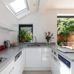 Small contemporary u-shaped open plan kitchen in London with a submerged sink, flat-panel cabinets, white cabinets, composite countertops, stainless steel appliances, porcelain flooring, beige floors, grey worktops and a breakfast bar.