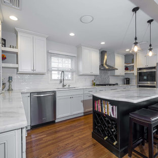 Photo of a large u-shaped kitchen/diner in New York with a submerged sink, flat-panel cabinets, white cabinets, quartz worktops, white splashback, porcelain splashback, stainless steel appliances, plywood flooring and an island.