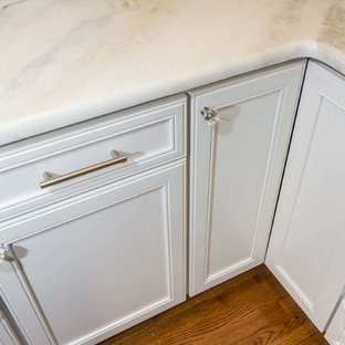 This is an example of a large u-shaped kitchen/diner in New York with a submerged sink, flat-panel cabinets, white cabinets, quartz worktops, white splashback, porcelain splashback, stainless steel appliances, plywood flooring and an island.