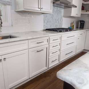 Large u-shaped kitchen/diner in New York with a submerged sink, flat-panel cabinets, white cabinets, quartz worktops, white splashback, porcelain splashback, stainless steel appliances, plywood flooring and an island.