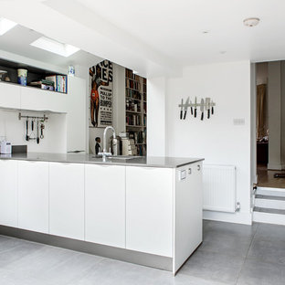 Design ideas for a medium sized contemporary enclosed kitchen in London with a submerged sink, flat-panel cabinets, white cabinets, grey floors, grey worktops, quartz worktops, glass sheet splashback and an island.