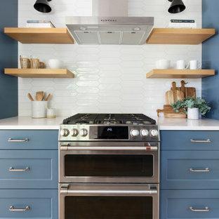 Inspiration för ett mellanstort vintage vit vitt kök, med en undermonterad diskho, luckor med infälld panel, blå skåp, bänkskiva i kvarts, vitt stänkskydd, stänkskydd i cementkakel, rostfria vitvaror och ljust trägolv