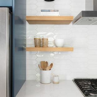 Inredning av ett klassiskt mellanstort vit vitt kök, med en undermonterad diskho, luckor med infälld panel, blå skåp, bänkskiva i kvarts, vitt stänkskydd, stänkskydd i cementkakel, rostfria vitvaror och ljust trägolv